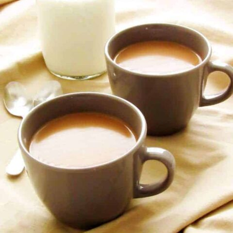 Coffee with Kahlua in two gray cups with a glass milk jug.