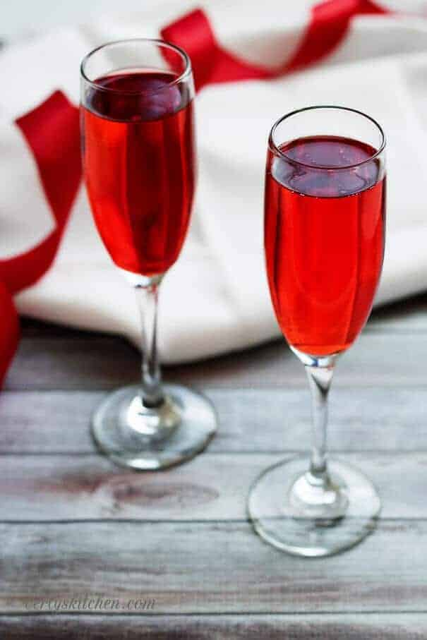 Champagne Grenadine Spritzer with a white napkin and red and white ribbons.