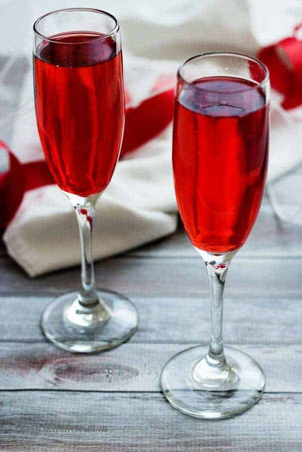 Two glasses of champagne in long stemmed wine glasses with a red ribbon.