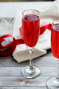 Champagne grenadine spritzer in a glass with red and white ribbons.