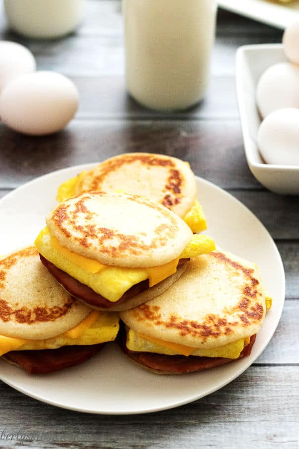Ham, egg, and cheese pancake sliders on a white plate.