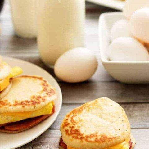 Ham, egg, cheese pancake sandwiches with fresh eggs and a bottle of milk.