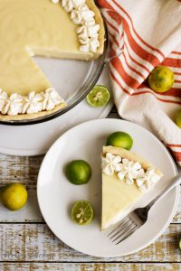Top down view of a slice of Key Lime Pie with key limes on a white plate.