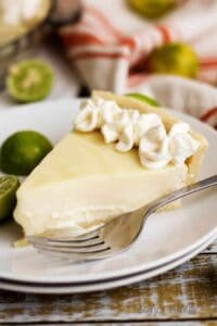 Slice of Key Lime Pie on a white plate.