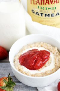 Single bowl of Strawberries and Cream Steel Cut Oatmeal with oatmeal container.