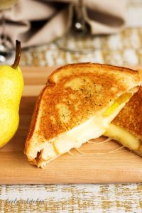 Grilled Brie and Pear Sandwich beside a fresh pear.