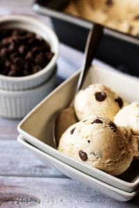 Homemade coffee ice cream with chocolate chips and a spoon in a square, white bowl.