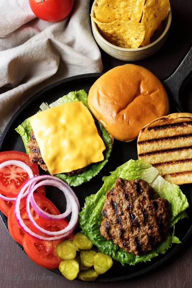Homemade Hamburgers on buns with toppings laid out.