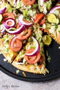 The Works Cheeseburger Pizza on a pizza pan.