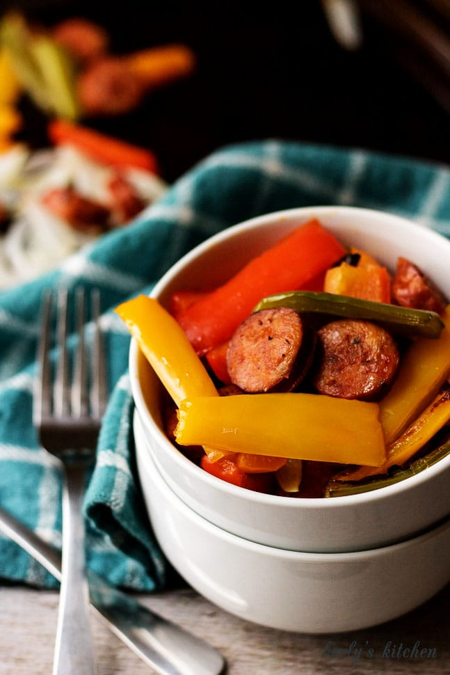 Sausage and peppers in a white bowl with forks.