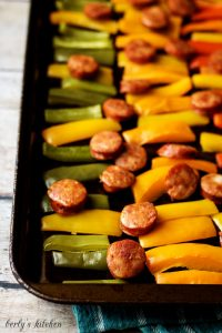 Cooked sausage and peppers on a baking sheet.