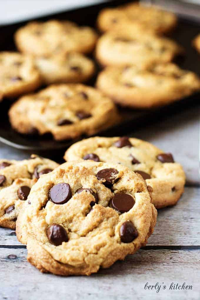 Pile of three peanut butter chocolate chip cookies in front of a pan of cookies.