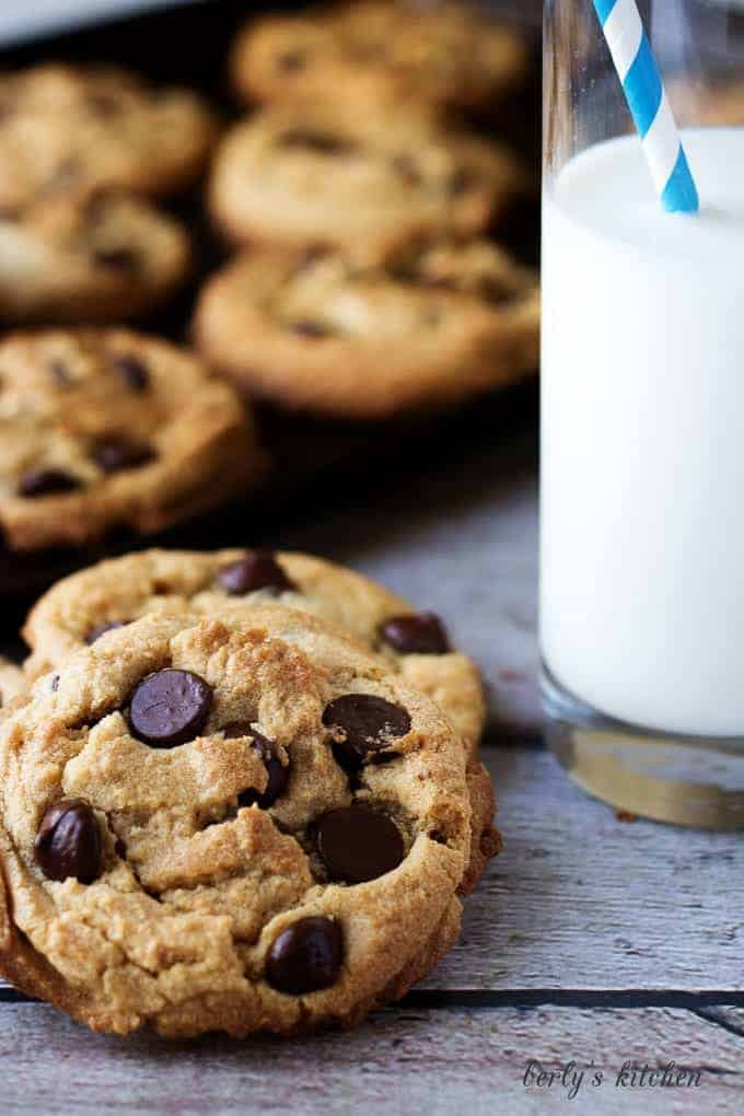 Chewy peanut butter cookies with dark chocolate chips next to a cup of milk.