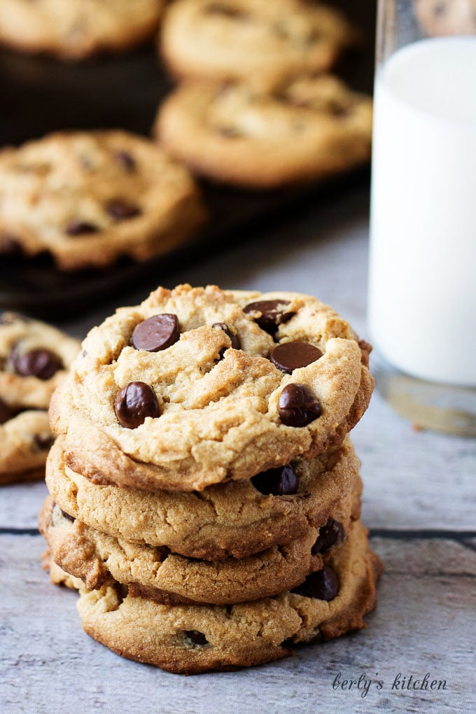 Stack of four chewy peanut butter cookies with chocolate chips.