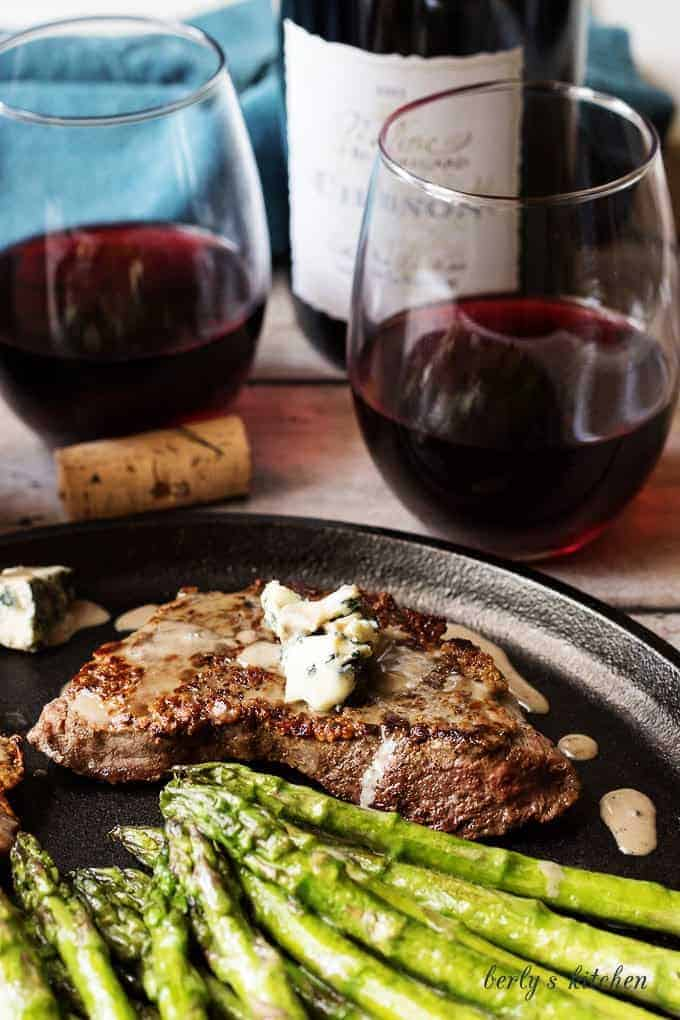Steak and asparagus with two glasses of red wine.
