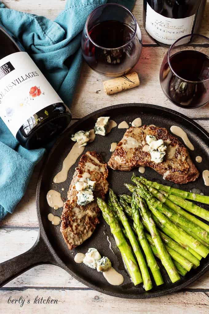 Top down view of steak, asparagus, blue cheese sauce with red wine.