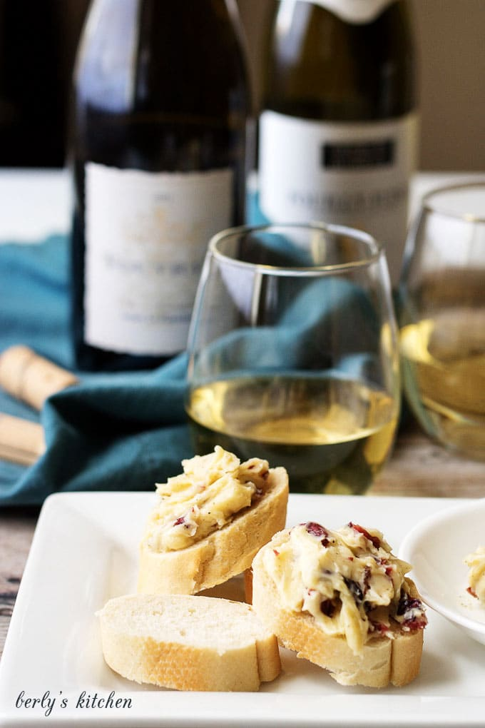 Cheese appetizers on a white plate with white wine.