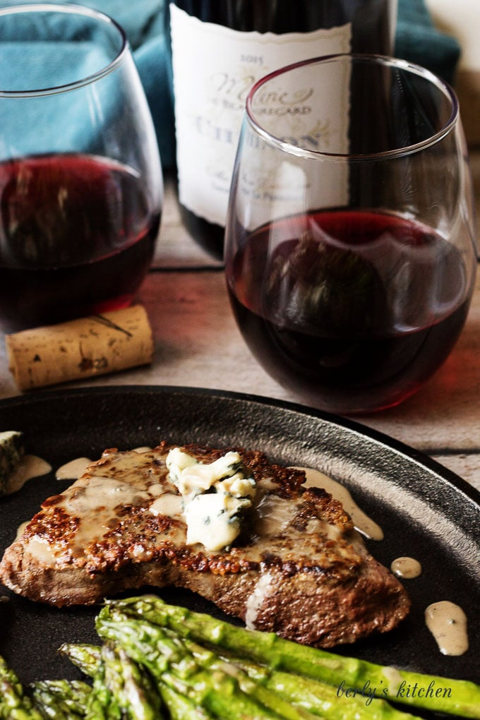 Close up of steak on cast iron with glasses of wine.