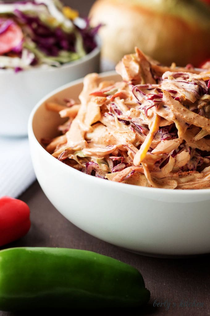 Spicy coleslaw recipe with white onion in the background.