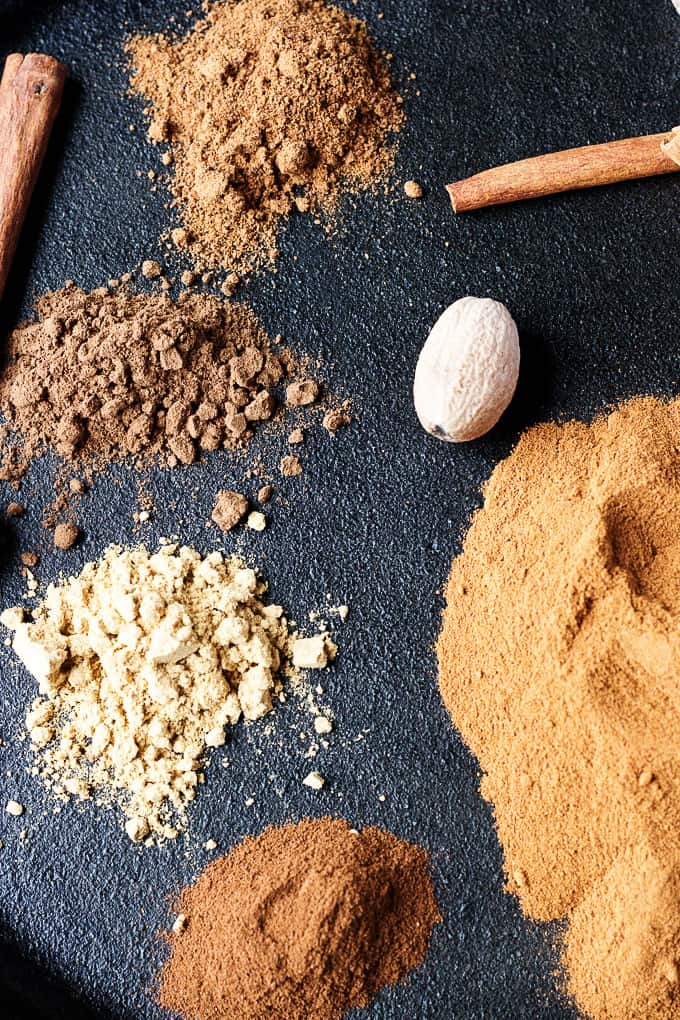 Close up of ground spices, whole nutmeg, and cinnamon sticks.