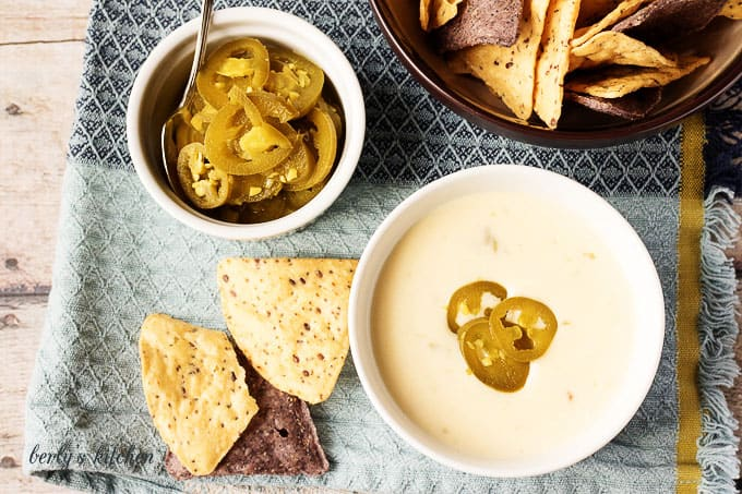 Top down view of cheese dip, jalapenos and spoon, and chips.