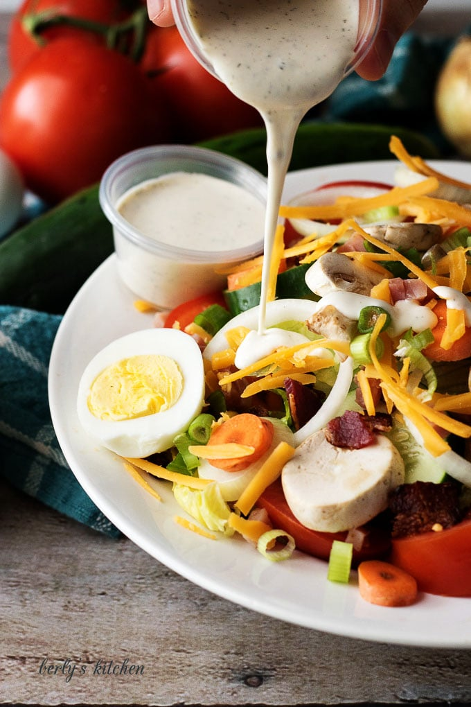 Chef salad with ranch dressing being poured on top.