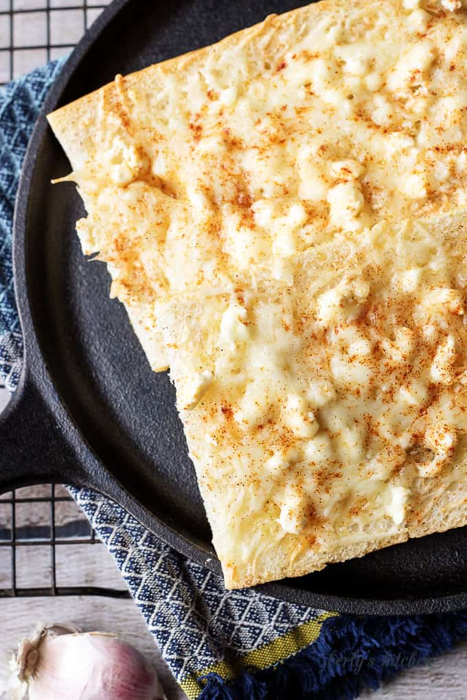 Top down view of feta mozzarella topped cheesy bread on a skillet.