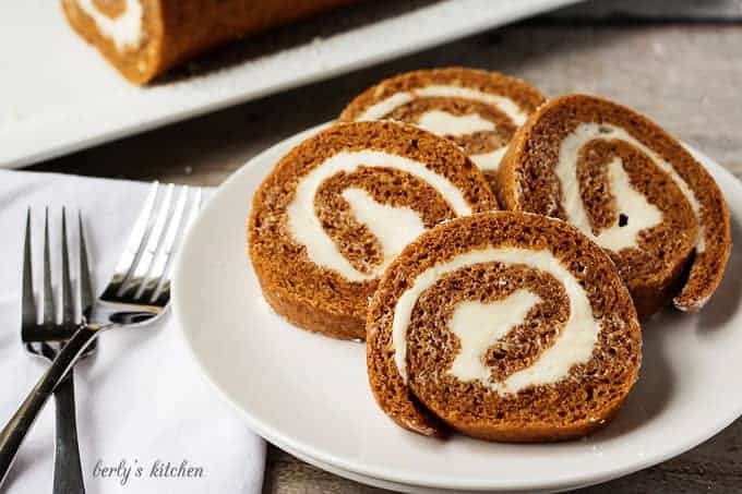 Four slices of pumpkin roll on a white plate with two forks.