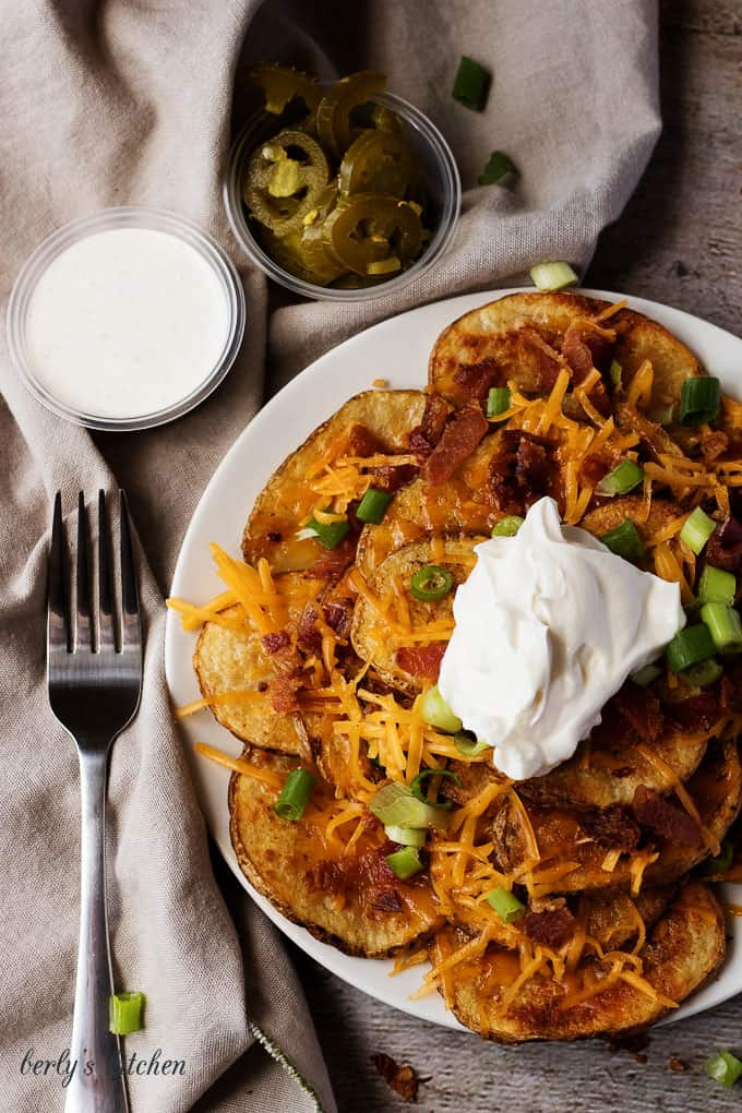 Top down view of sliced potato nachos with cheese, bacon, and a side of ranch and jalapenos.