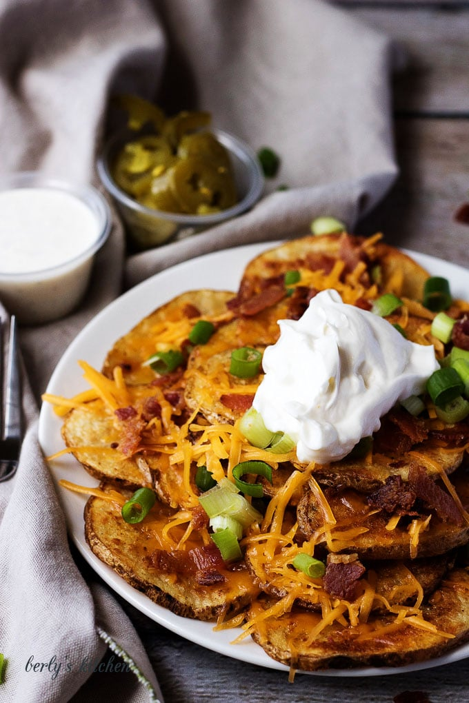 Plate of loaded potato nacho fries with cup of jalapenos in the background.