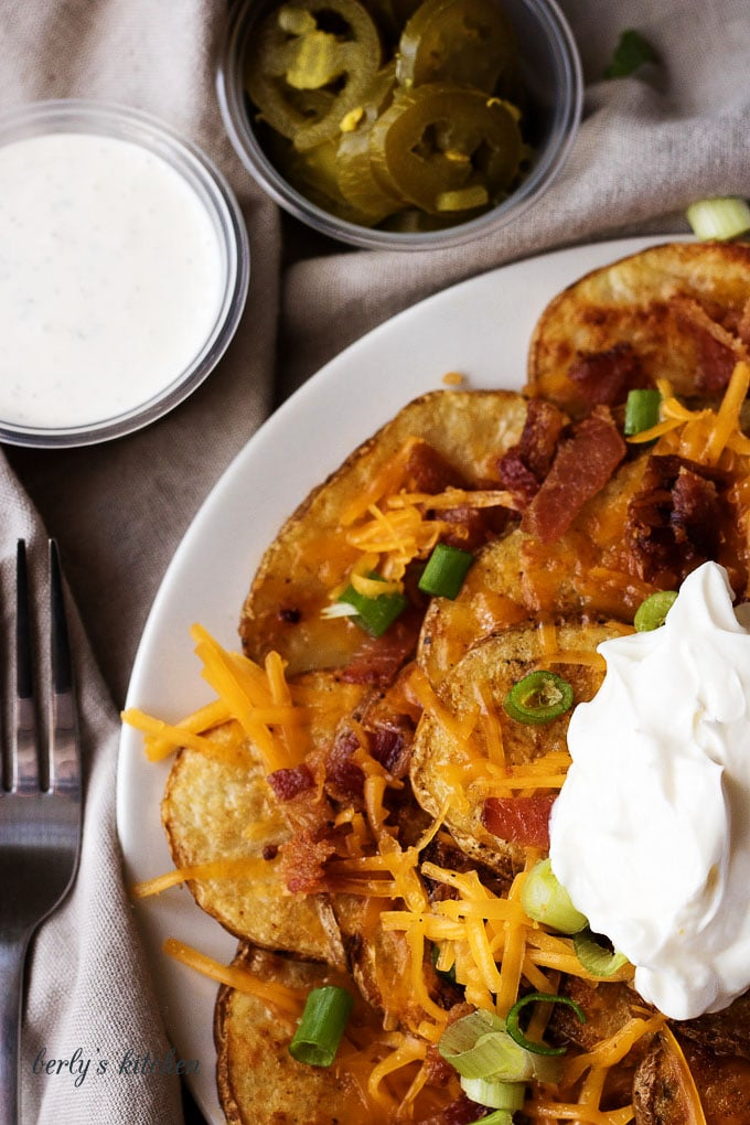 Close up of loaded potato nachos on a white plate.