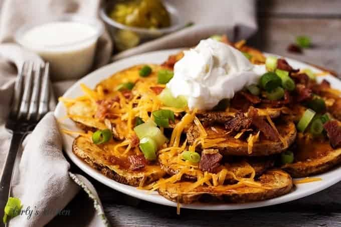 Sliced potato fries topped with cheese, bacon, and sour cream.