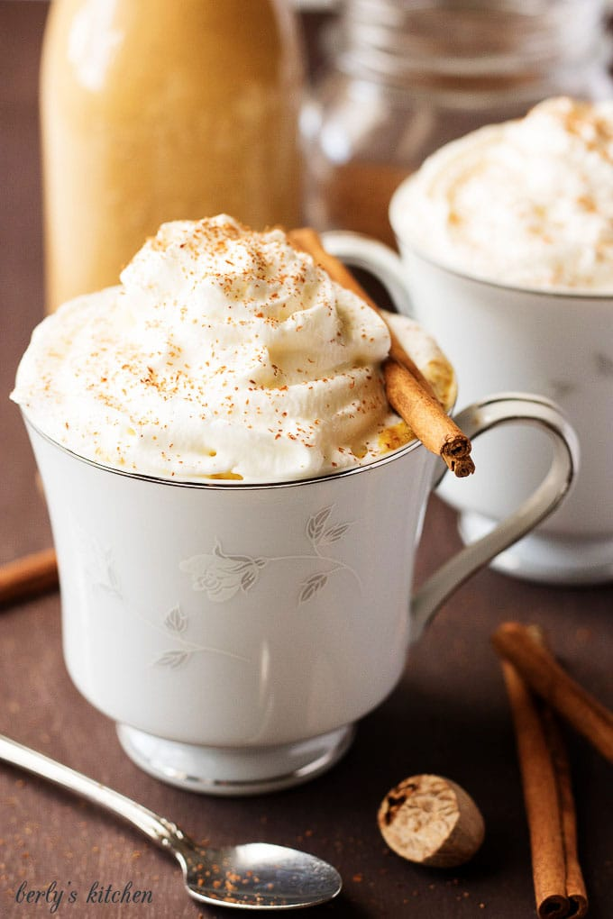 Pumpkin spice latte topped with whipped cream and cinnamon stick.