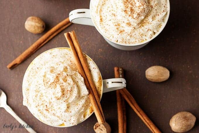 Two cups of pumpkin spice latte with cinnamon sticks.