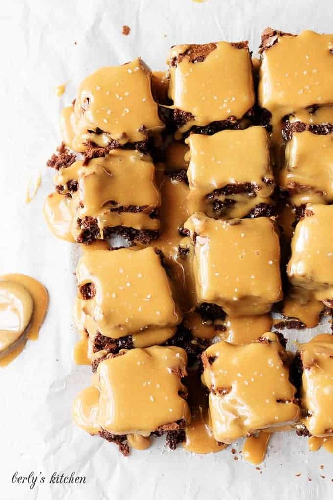Brownies with salted caramel sauce on parchment paper.