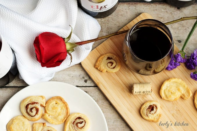 Crackers, rose, and glass of wine on a cutting board.