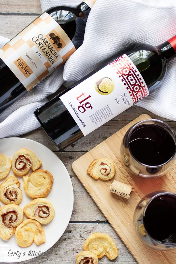 Two bottles of red wine with crackers.