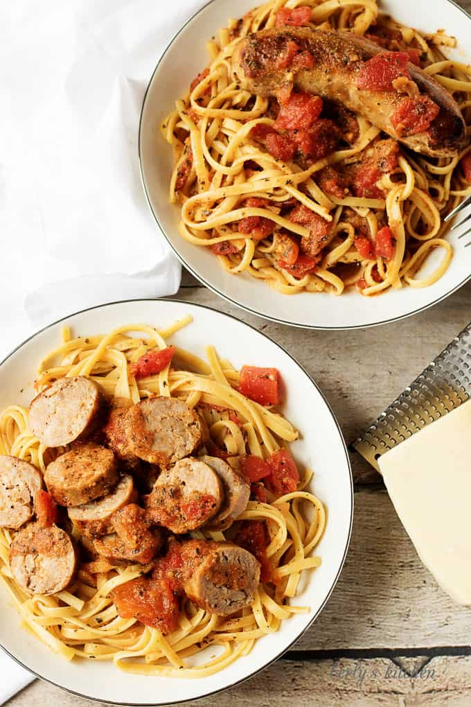Top down view of two bowls of sausage linguine with Parmesan cheese.