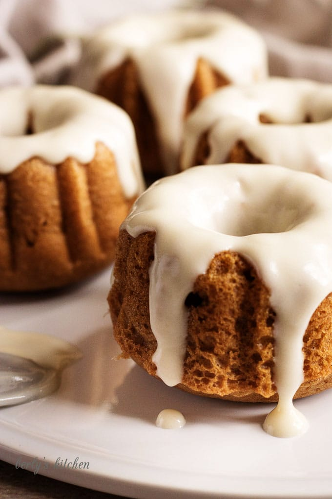 Mini pumpkin bundt cakes with maple buttercream on a white plate.