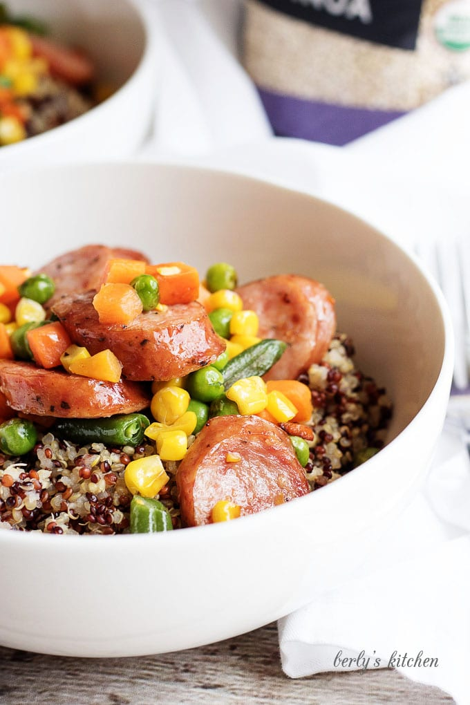 Close up of organic quinoa sausage dinner in a white bowl.