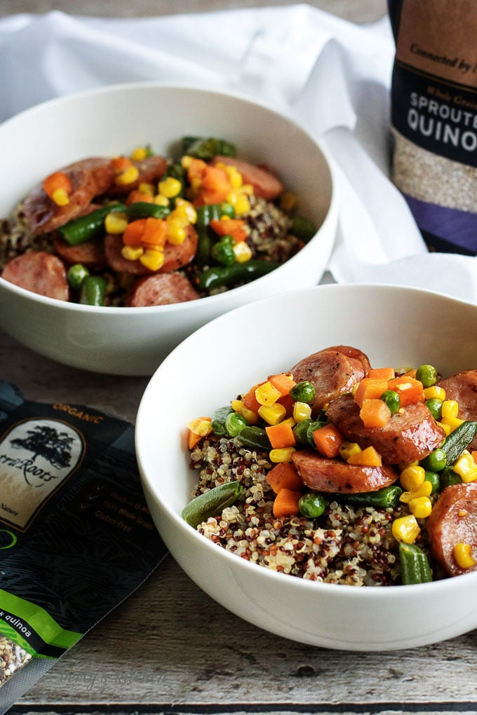 Two white bowls filled with corn, green beans, sausage and quinoa.