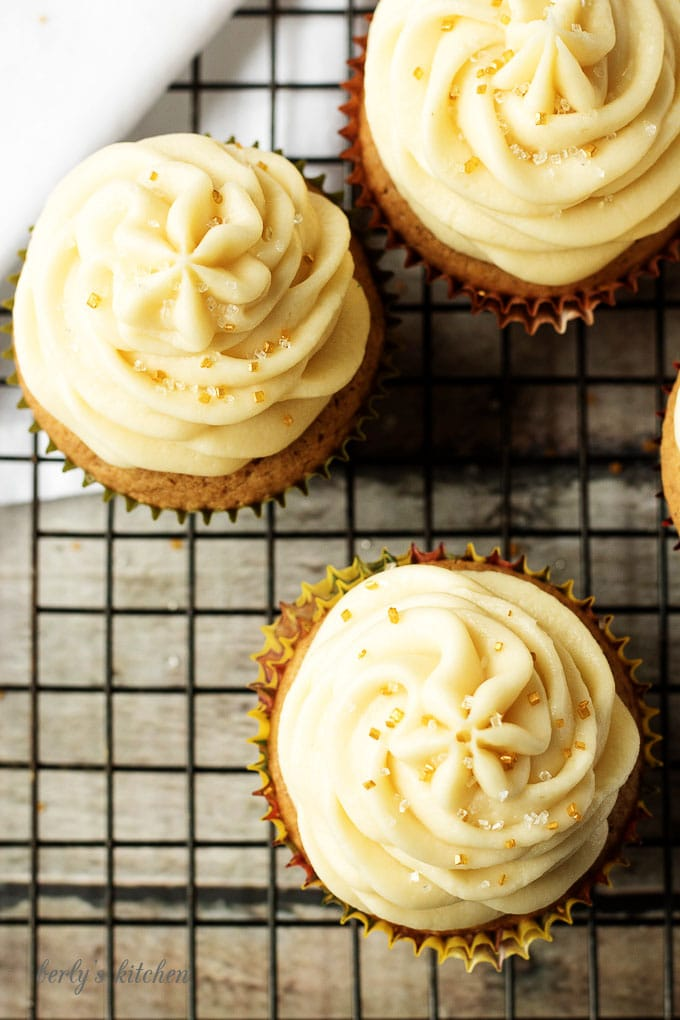 Top down view of spice cupcakes with maple frosting and sprinkles.