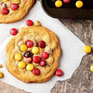 Top down view of M&M chocolate chip cookies with scattered M&Ms.