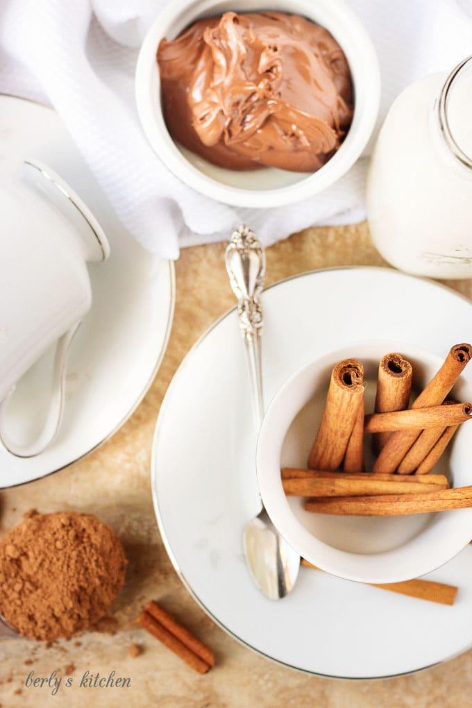 Ariel view of hazelnut spread, cocoa, and cinnamon sticks used in hot cocoa.