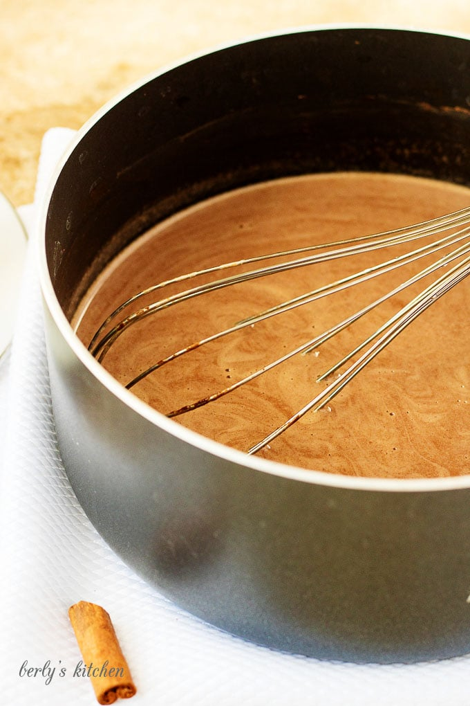 The hot cocoa being whisked in a saucepan.
