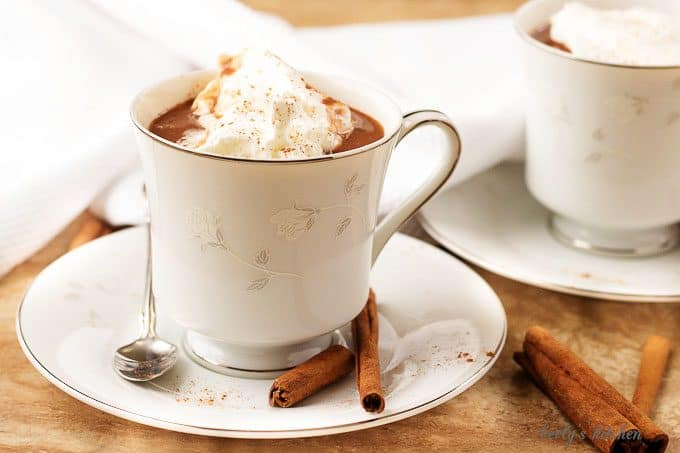 A cup of hot cocoa garnished with whipped cream.