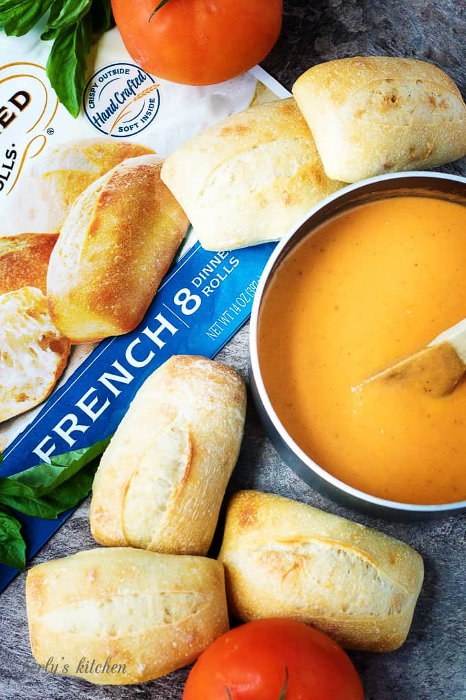 Tomato soup in a saucepan with dinner rolls.