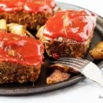 Mini meatloaves topped with ketchup next to two forks.