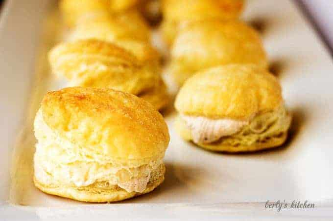 Rows of cream puffs stuffed with pumpkin spiced cream cheese on a white plate.