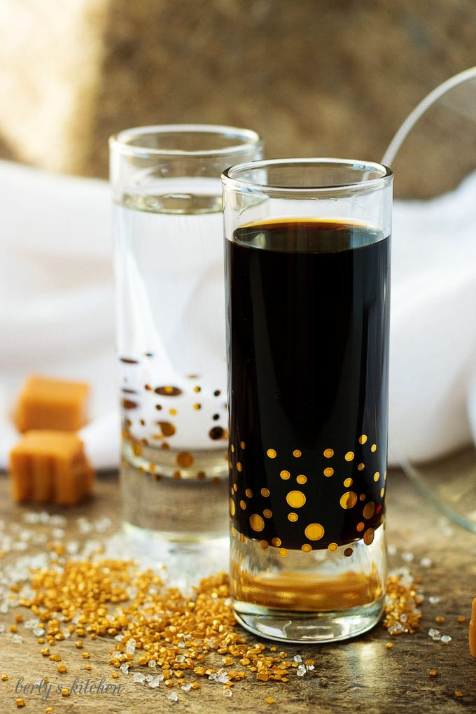 Coffee liqueur and gin in shot glasses with gold and white decorating sugar.